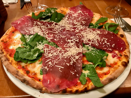 Bresaola Pizza with Parmesan Cheese, Rocket Leaves or Arugula / Rucola. Traditional Food.