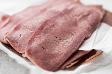 Sliced Beef Tongue Slices on Paper. Organic Smoked Meat.