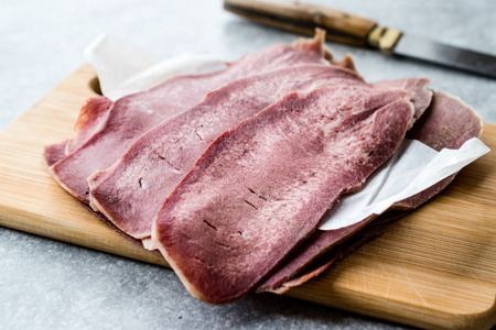 Sliced Beef Tongue Slices on Wooden Board. Organic Smoked Meat.