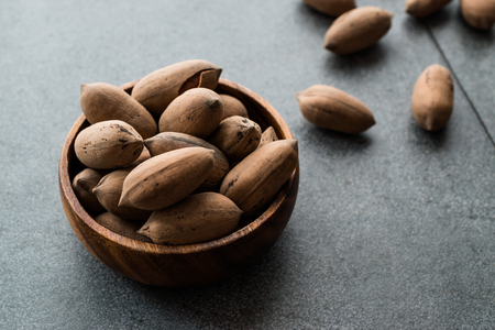 Pecan Nuts with Shell in Wooden Bowl  Walnuts. Organic Food.