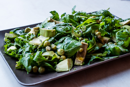 Avocado Salad with Green Peas and Rocket Leaves in Rectangular Plate  Arugula or Rucola Leaves. Organic Fresh Food.