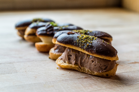 French Dessert Chocolate Eclairs with Cream Filled and Pistachio Powder  Profiteroles. Traditional Dessert. Stock Photo