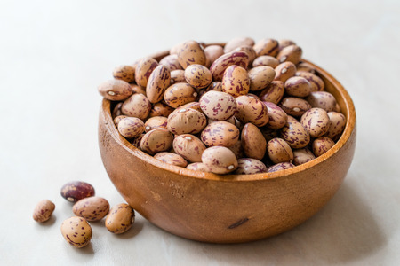 Raw Dry Pinto Beans on Marble Board with Wooden Bowl  Kidney Beans. Organic Food. Stock Photo