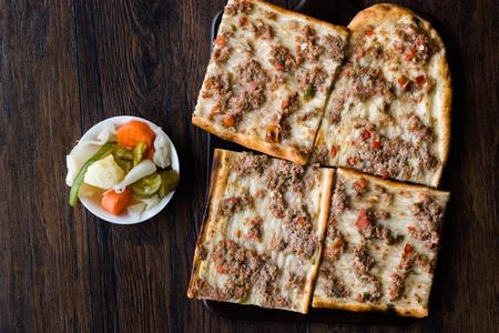 Turkish and Arabic Traditional Ramadan Bread Sliced Etli Ekmek Kebab with Minced Meat (Pide or Lahmacun Kebap) serving on wood by Konya or Sivas Stock Photo