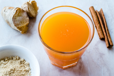 Jamu Healthy Asian Drink with Turmeric and Cinnamon Stick, Orange Juice. Traditional Beverage.