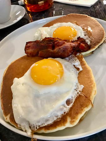 Salted Pancakes with Hollandaise Sauce, Eggs and Crispy Bacon for Breakfast. Salty Organic Traditional Fast Food.