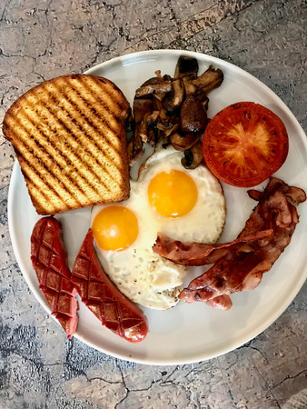 Aussie  Australian Breakfast with Brioche Toast, Fried Eggs, Crispy Bacon Sausage and Mushrooms. Traditional Food. Stock Photo