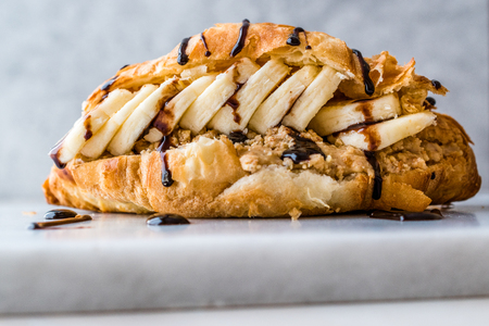Croissant Sandwich with Banana, Peanut Butter and Chocolate Sauce for Breakfast.