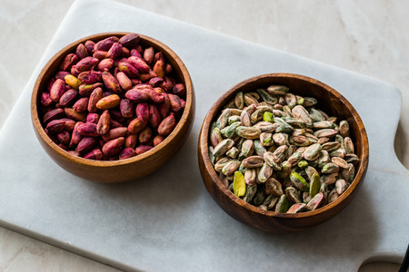 Raw and Roasted Wooden Bowl of Peeled Pistachios without Shell / with No Shell. Organic Food.