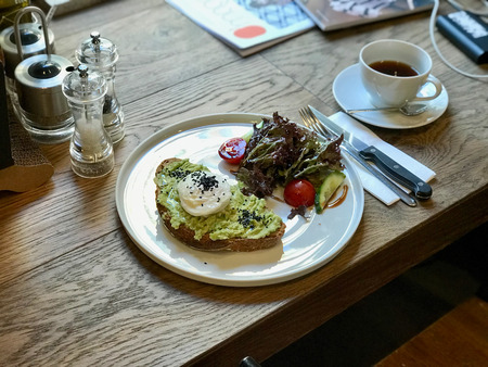 Avocado Egg Benedict with Poached Egg with Coffee at Cafe Shop on Wooden Table for Breakfast. Banque d'images