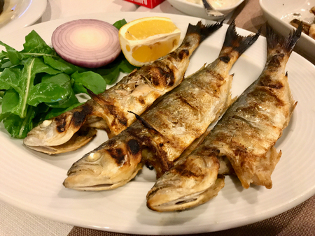 Chinese Fish Cinekop  Sarikanat Bluefish at Restaurant Served with Onions and Salad from Istanbul Turkey. Organic Food.