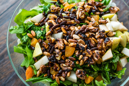 Pine Nut Salad with Walnut, Pear, Dried Apricot, Arugula or Rucola Leaves in Glass Bowl. Organic Food.