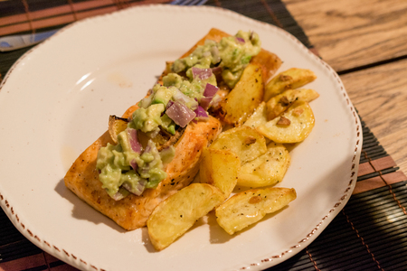 Salmon Fillet with Avocado in Plate at Dinner Table. Organic Seafood.