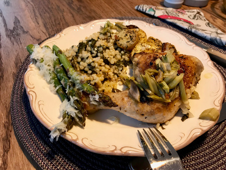 Couscous with Chicken Legs, Chard, Asparagus, Potatoes and Parmesan Cheese in Plate. Organic Food.