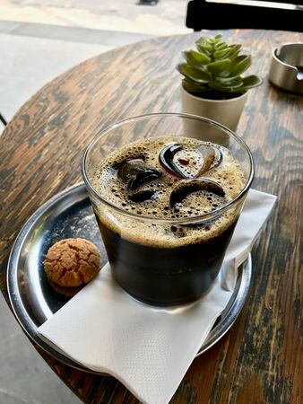 Cold Brew Coffee with Ice at Cafe Shop served with Cookie on Wooden Table. Organic Beverage. Reklamní fotografie - 124568487