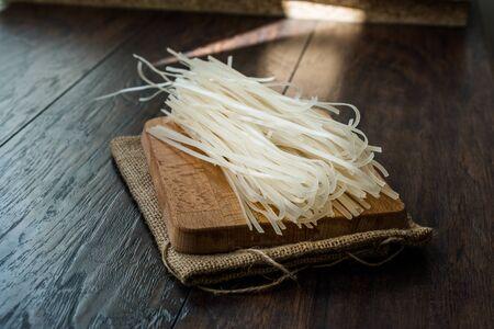 Nouilles de riz crues sur sac de serviettes en lin prêt à l'emploi. Nourriture traditionnelle biologique.