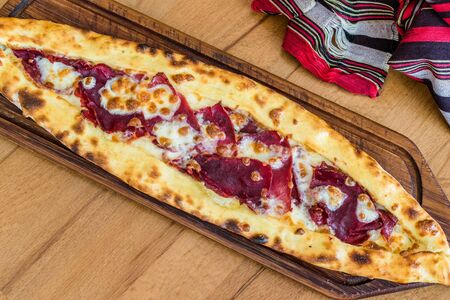 Traditional Turkish Pide at Kebab Restaurant on Wooden Table. Turkish Pizza. Stock Photo