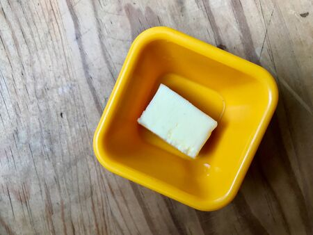 Butter Piece in Yellow Plastic Cup Ready to Use. Organic Food.