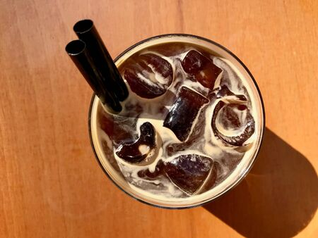 Cold Brew Coffee Americano with Ice at Cafe Shop served on Wooden Table. Organic Beverage.