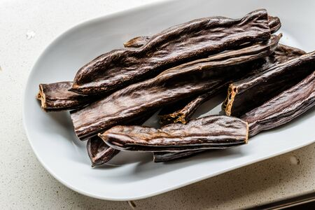 Ripe Carob Pods in Plate Ready to Eat. Organic Food.