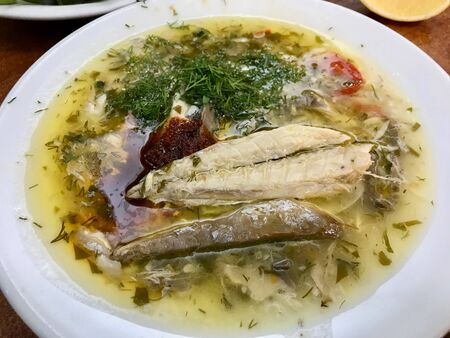 Turkish Style Fish Soup with Spices and Herbs served at Local Restaurant. Healthy Organic Food.