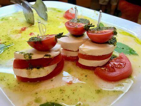 Italian Caprese Salad as Appetizer with Olive Oil, Mozzarella Cheese and Sliced Tomato Slice with Food Skewers. Organic Fresh Food.