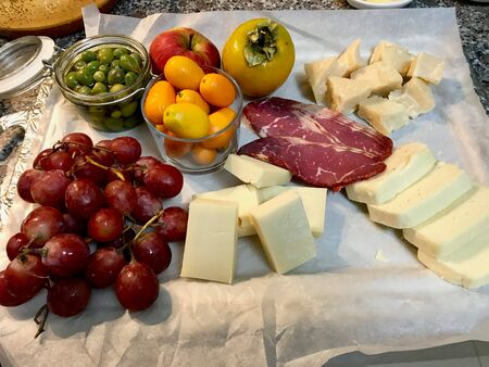 Red Wine And Assorted Cheese Plate, Smoked Beef, Ham, Salami, Green Olives, Fresh Ripe Persimmon with Fruit for Party. Ready to Eat.