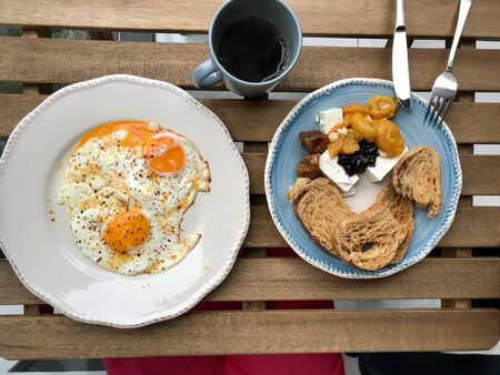 Homemade Turkish Style Breakfast with Fried Eggs, Cheese, Bread and Jam  Marmalade served with Filtered  Filter Coffee on Wooden Table. Traditional Dish.
