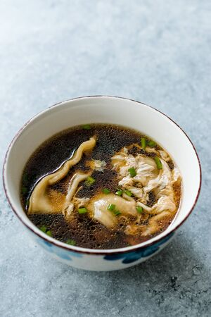 Asian Food Wonton Soup with Bok Choy and Chives in Porcelain or Ceramic Bowl. Traditional Dish Cuisine.