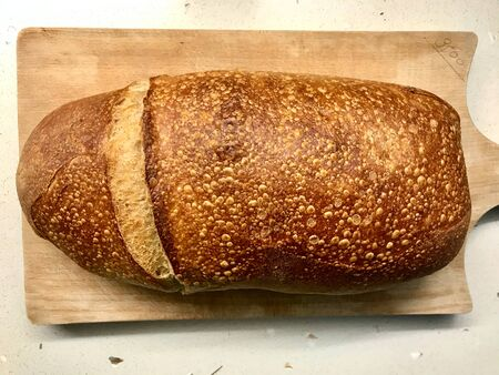 Whole Ciabatta Sourdough Bread with Olive Oil on Wooden Board. Organic Bakery Food. Фото со стока