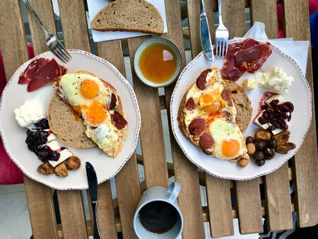 Turkish Breakfast with Fried Eggs, Sucuk, Pastirma  Pastrami, Honey, Cheese and Bread Slices. Traditional Organic Food.