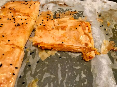 Turkish Pastry Borek with Pumpkin and Cumin Seeds on Baking Paper  Sheet.