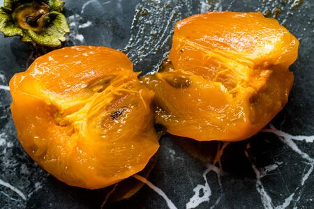 Half Cut Raw Organic Juicy Persimmon Fruit Ready to Eat on Dark Black Granite Surface. Healthy Food.