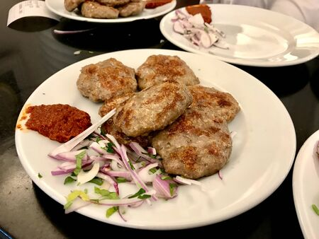 Turkish Meatballs Kofte / Kofta with Onions and Red Hot Chili Tomato Paste Sauce served with Plate.