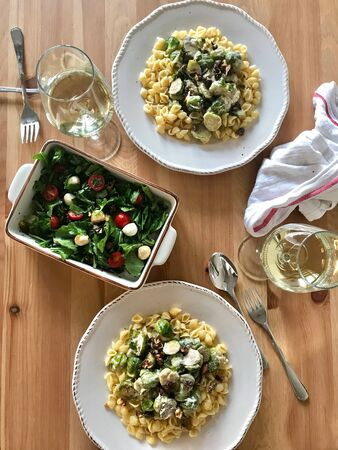 Conchiglie  Conchiglioni Homemade Pasta with Brussel Sprouts and Salad on Wooden Table. Ready to Eat. Organic Traditional Food.
