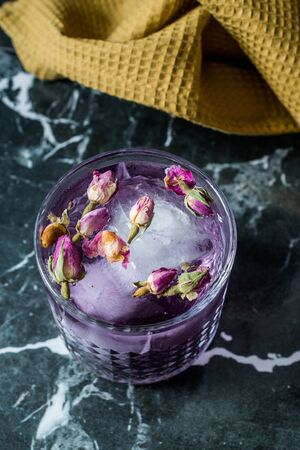 Pink Gin Tonic Cocktail with Dried Rose Buds and Ice in Glass Cup. Ready to Drink.