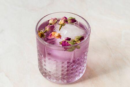 Cocktail rosa gin tonic con boccioli di rosa essiccati e ghiaccio in una tazza di vetro. Pronto da bere.