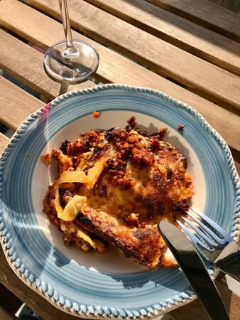 Homemade Lasagna with Red Wine on Wooden Table Outside / Outdoor. Traditional Food. Фото со стока - 134228008