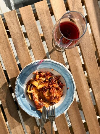 Homemade Lasagna with Red Wine on Wooden Table Outside / Outdoor. Traditional Food. Фото со стока - 134228010
