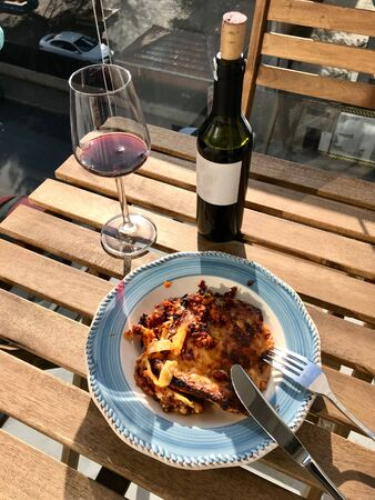 Homemade Lasagna with Red Wine on Wooden Table Outside / Outdoor. Traditional Food. Фото со стока - 134228013