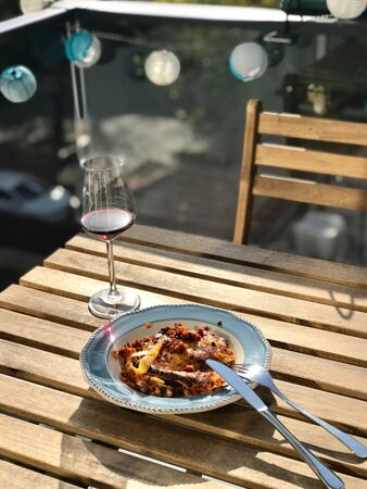 Homemade Lasagna with Red Wine on Wooden Table Outside / Outdoor. Traditional Food. Фото со стока - 134228040