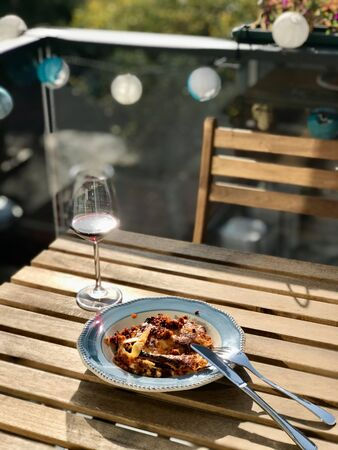 Homemade Lasagna with Red Wine on Wooden Table Outside / Outdoor. Traditional Food. Фото со стока - 134228042