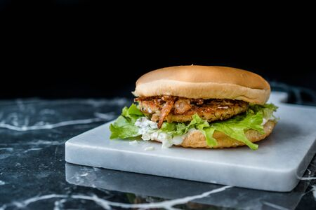 Homemade Salmon Burger with Tartar Sauce, Onion and Lettuce on Marble Board. Ready to Eat.