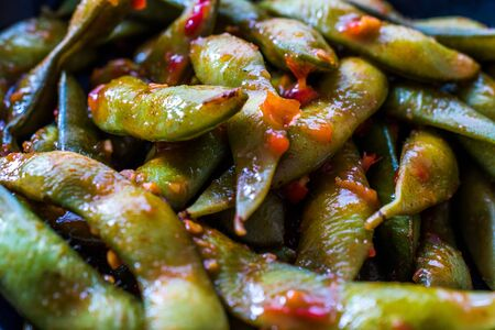 Spicy Sambal Edamame with Chopsticks / Spiced Style with Red Hot Chili Sauce. Traditional Organic Food. Banque d'images