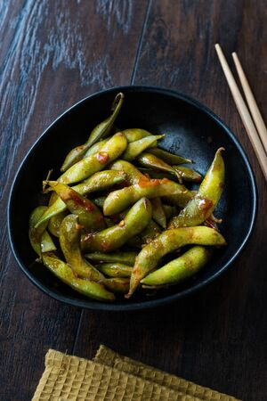 Spicy Sambal Edamame with Chopsticks / Spiced Style with Red Hot Chili Sauce. Traditional Organic Food. Stock Photo