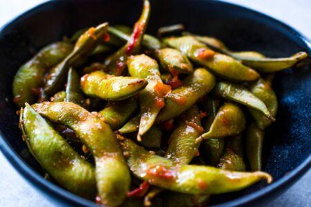 Edamame Sambal piccante con bacchette / Stile speziato con salsa di peperoncino rosso piccante. Cibo biologico tradizionale.