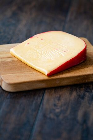 Hard Dutch Gouda Cheese, Close-up on Wooden Board with Knife. Organic Traditioal Food.