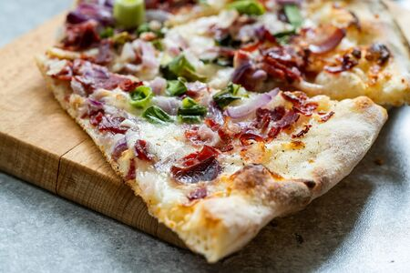 Flammkuchen Pizza Slices  Traditional Tarte Flambee with Creme Fraiche, Cream Cheese, Bacon and Red Onions on Wooden Board. Traditional Fast Food.