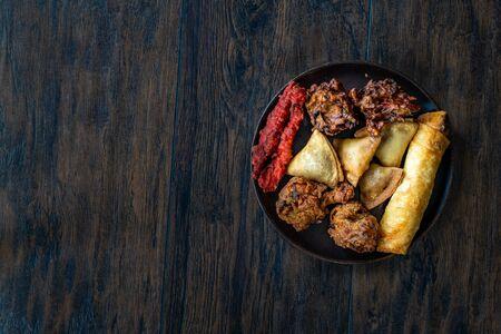 Indian Food Plate with Chicken Pakora, Aloo Tikki, Samosas Samsa and Spring Rolls. Traditional Food.
