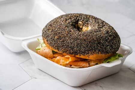 Take Away Salmon Bagel Sandwich with Lox Cream Cheese and Poppy Seeds in Plastic Container Box Package. Organic Healthy Fast Food.